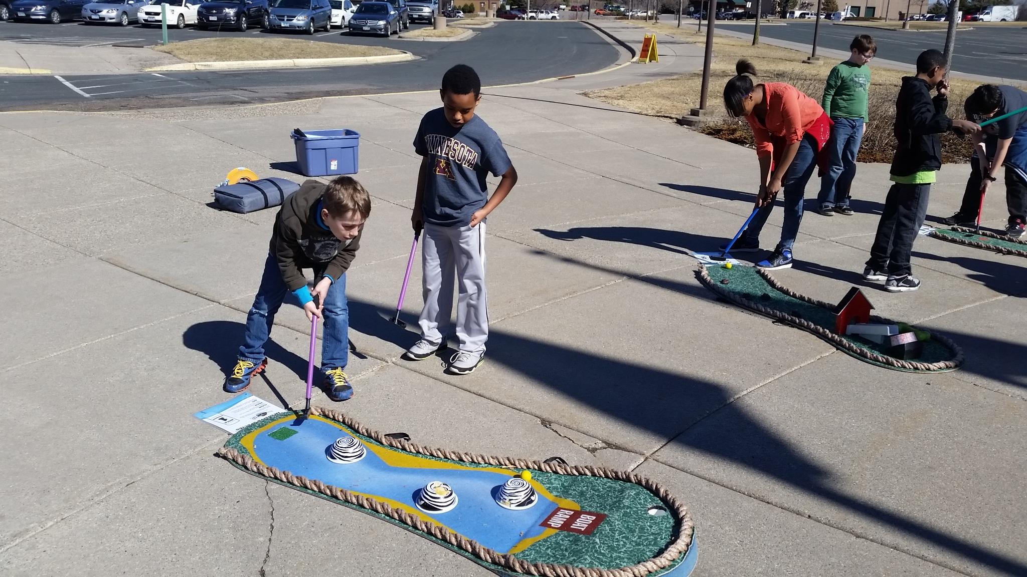 Kids playing putt putt in a parking lot
