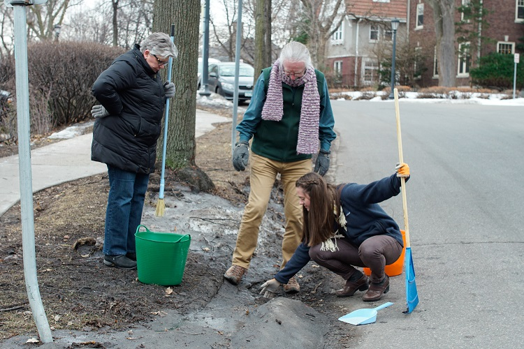 2 women and a man cleaning a storm drain in late winter