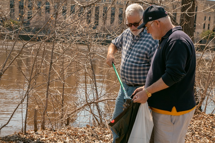 Two men cleaning up litter long the river