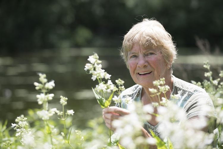 Woman smiling behind native flowering plants