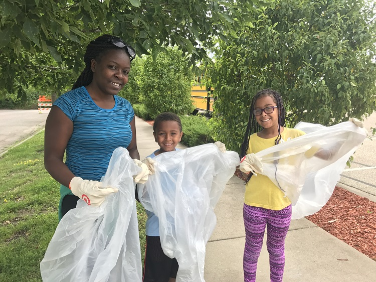 Young family picking up trash during Greenway Cleanup