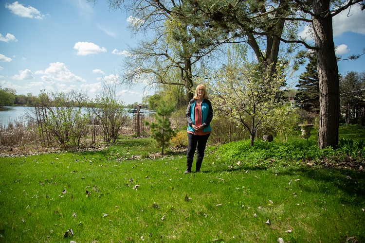Woman standing in front of shoreline garden