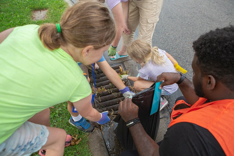 Kids clearing a storm drain of debris