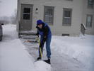 Woman shoveling snow off a sidewalk