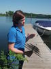 Kelly Dooley holding a zebra mussel plate on a dock