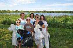 Group of adults and kids holding garbage bags in front of Lake Hiawatha