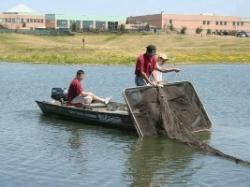 2 people in boat with large net