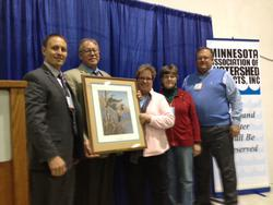 5 people with one holding a framed award