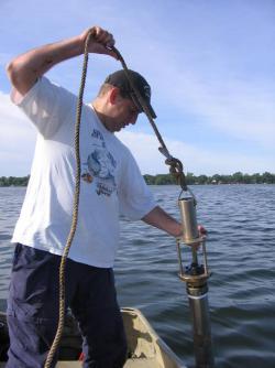Man taking a soil core sample out of a lake